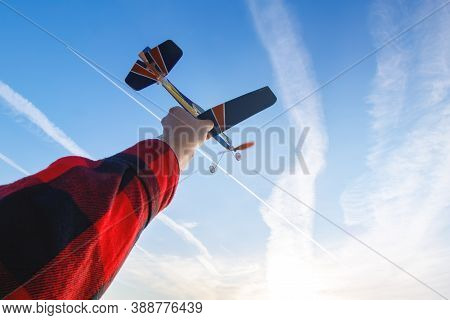 A Model Of A Rubber-engined Paper Toy Airplane In Hand Against A Blue Sky With Clouds And A сontrail