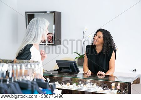 Happy Friendly Seller Talking To Customer In Jewelry Store. Woman Consulting Shop Assistant At Showc