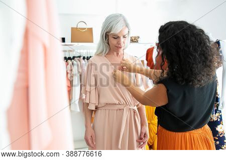 Female Shop Seller Helping Customer To Try On New Dress. Woman Choosing Clothes In Fashion Store. Bu