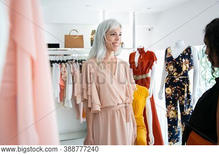 Happy Customer Trying On New Dress In Boutique. Woman Choosing Clothes In Fashion Store. Buying Clot