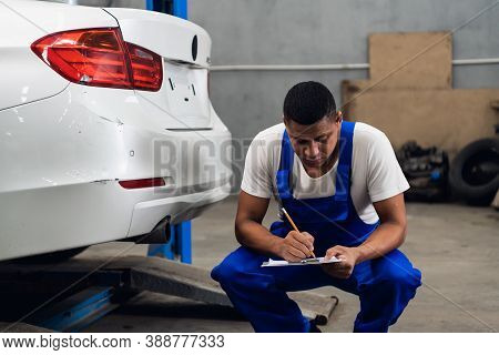 A Car Service Worker In Overalls Inspects A Car In A Workshop