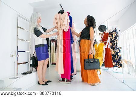Focused Female Customer And Shop Assistant Browsing Dresses On Rack Together, Choosing Clothes In Fa