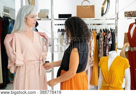 Shop Seller Adjusting New Dress On Female Customer. Woman Trying On Clothes In Fashion Store. Buying