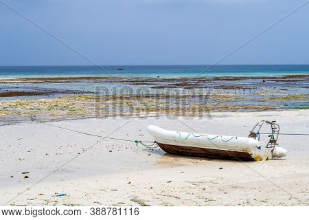 Small Boat (dinghy) Anchored On A White Sandy Empty Beach On The Coast Of Pemba Island, Tanzania, Wi