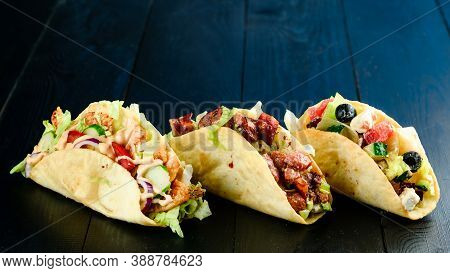 Three Mexican Tacos With Beef And Vegetables On Wooden Dark Background. Mexican Dish With Sauces Gua