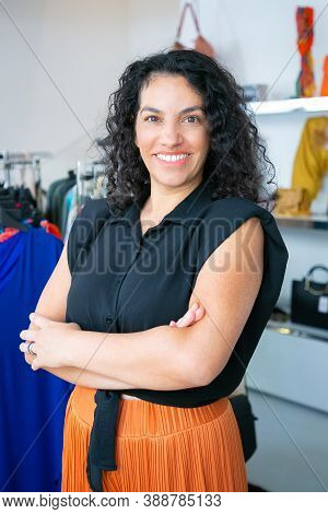 Cheerful Latin Black Haired Woman Standing With Arms Folded Near Rack With Dresses In Clothes Shop,