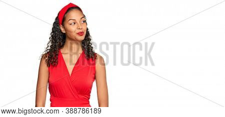 Young african american girl wearing elegant and sexy look smiling looking to the side and staring away thinking.