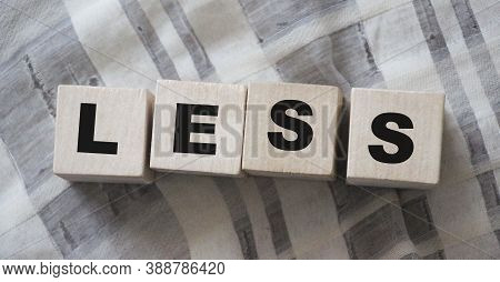 Less Word On Wooden Cubic Blocks With Letters. Spend Less Or Cut Costs Business Concept