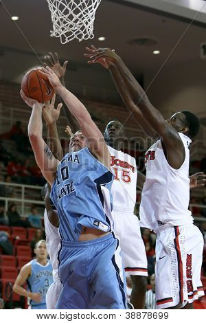 NEW YORK-NOV 3: Sonoma State Seawolves forward Brandon Glanz shoots a basket under St. John's Red Storm guard Sir'Dominic Pointer (15) at Carnesecca Arena on November 3, 2012 in Jamaica, Queens, New York.