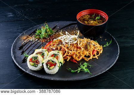 Asian Food Table With Various Kind Of Chinese Food, Noodles, Chicken, Rolls, Sushi. Served On Old Wo