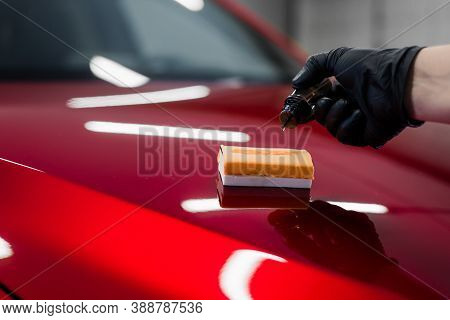 Car Detailing - Man Applies Nano Protective Coating Or Wax On Red Car. Covering Car Bonnet With A Li