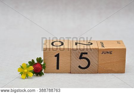 15 June On Wooden Blocks With A Strawberry And Yellow Flower On A White Background