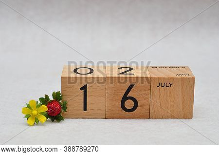16 July On Wooden Blocks With A Strawberry And Yellow Flower On A White Background