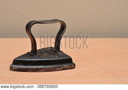 An Antique Iron Placed Flat On A Table