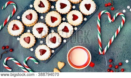 Top Panoramic View Of Christmas Linzer Cookies Filled With Jam. Panoramic Composition On Dark Wood.