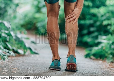 Runner leg injury painful leg. Man massaging sore calf muscles during running training outdoor from pain.