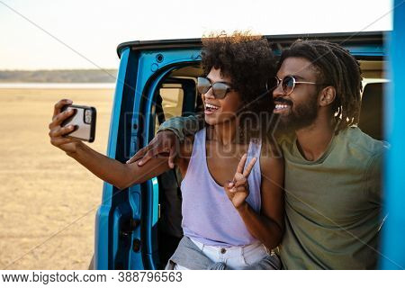 Young couple in love making selfie using smart phone while sitting on a back of car