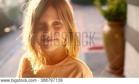 Portrait of happy cute 8 year old girl child looking at camera outdoors on sunny patio. Closeup, shallow DOF.
