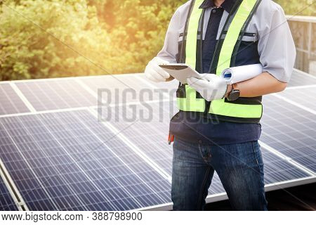 A Male Engineer Holds A Tablet To Inspect The Solar Cell System. That Is On The Building. Concept Of