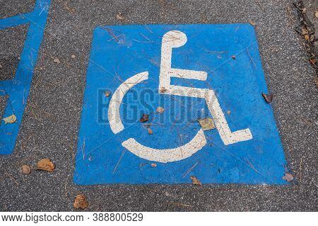 Blue With The Universal Handicap Symbol Signage Painted On The Ground In A Parking Lot At A Park For