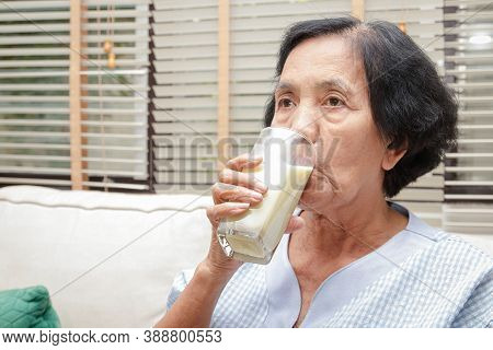 Elderly Asian Women Drink Milk Containing Calcium To Prevent Osteoporosis. Make The Body Strong And