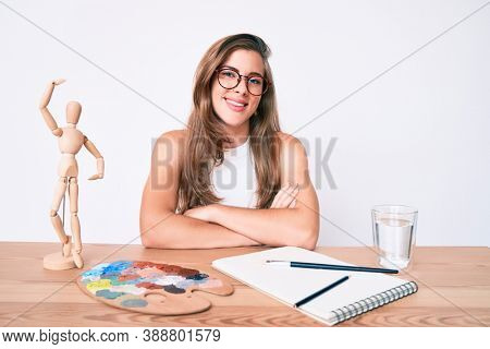 Beautiful young caucasian woman artist painter sitting on desk happy face smiling with crossed arms looking at the camera. positive person.