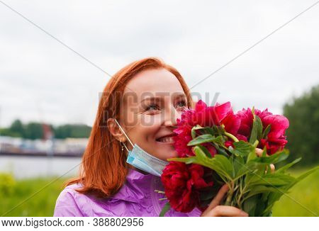 Revival After Coronavirus. Smiling Happy Redhead Woman Sniffs Pink Flowers With Pulled Down Medicine