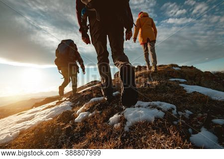 Small Group Of Tourists Walks At Mountain Top At Sunset Time. Close Up Photo