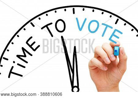 Hand Writing Time To Vote On A Clock With Blue Marker On Transparent Wipe Board On White Background.