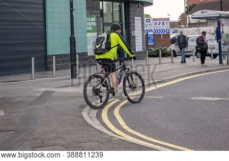 Doncaster,yorkshire, England - October 7, 2020. Cyclist Riding A Bicycle With A Backpack On His Back