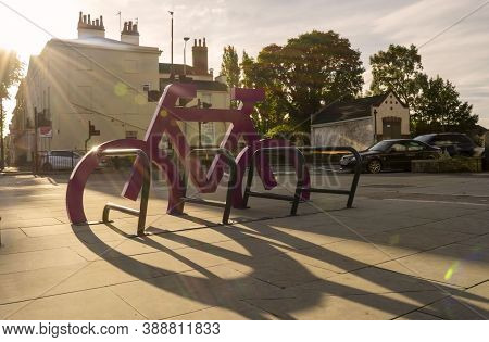 Doncaster,yorkshire, England - October 7, 2020. Pink Bicycle Sculpture Against The Sun's Rays.