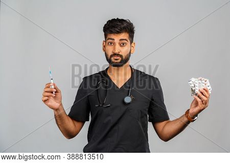 Cute Indian Doctor Or Surgeon In Black Uniform With Stethoscope, Syringe And Pills On Gray Backgroun