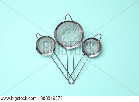 Different Skimmers On Turquoise Background, Flat Lay. Cooking Utensils