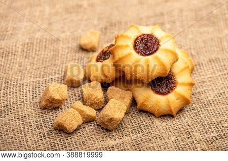 Homemade Pastry Cookies With Jam And Pieces Of Brown Cane Sugar On A Background Of Homespun Fabric W