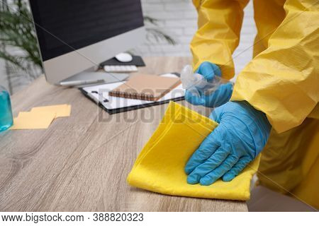 Janitor In Protective Suit Disinfecting Office Furniture To Prevent Spreading Of Covid-19, Closeup