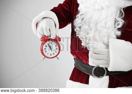 Santa Claus Holding Alarm Clock On Light Grey Background, Closeup. Christmas Countdown