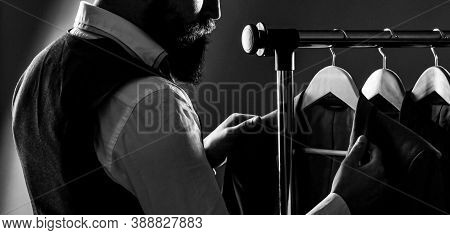 Stylish Mens Suit. Man Suit, Tailor In His Workshop. Male Suits Hanging In A Row. Men Clothing, Bout