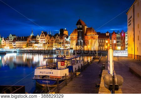 Gdansk, Poland - October 8, 2020: Architecture of the old town in Gdansk over Motlawa river at night, Poland. Gdansk is the historical capital of Polish Pomerania with medieval old town architecture.