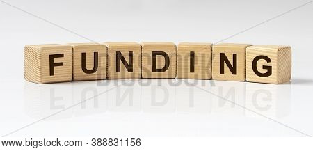 Funding Word Written On Wooden Cube Blocks On White Glossy Background.