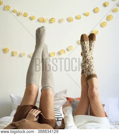 The Concept Of A Pajama Party And New Years Holidays. Girls In Leggings Without Faces On The Bed Rai