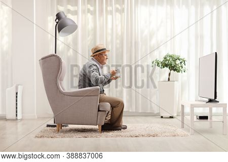 Elderly man with a cup sitting in an armchair and watching tv at home