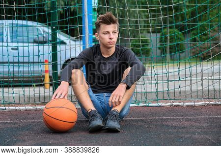 Outdoor Portrait Of Teenage Boy With Ball On Street Basketball Court, Trendy Male 16, 17 Years Old L