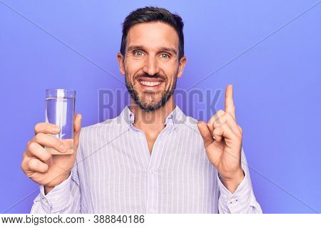 Young handsome man drinking glass of water to refreshment over isolated purple background smiling happy pointing with hand and finger to the side