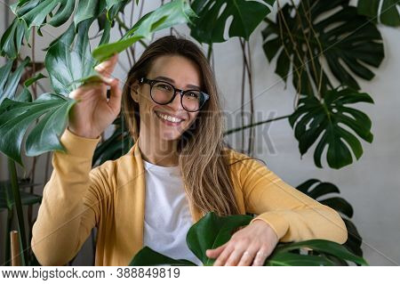 Happy Young Woman With Natural Makeup In Eyeglasses Standing Among Monstera Leaves In Green House, T