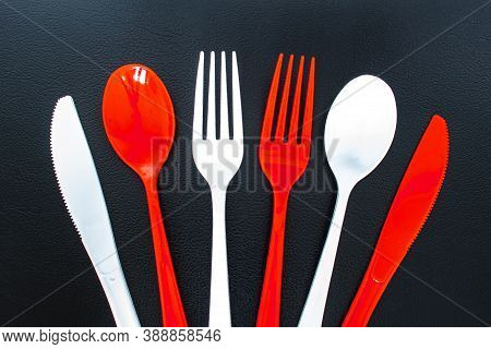 Single Use Red And White Plastic Cutlery On A Leather Background. Concept: Ban Single Use Plastic
