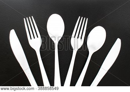 Single Use White Plastic Cutlery On A Leather Background. Concept: Ban Single Use Plastic