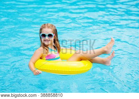 Child In Swimming Pool Floating On Toy Ring. Kids Swim. Colorful Yellow Float For Young Kids.