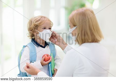 Family With Kids In Face Mask Going To School Or Kindergarten. Mother And Child Wear Facemask During
