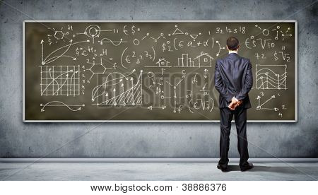 Business person standing against the blackboard with a lot of data written on it