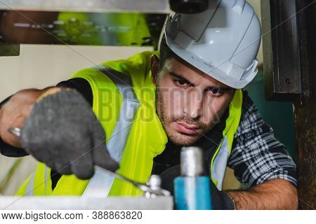 A Caucasian Male Mechanical Engineer Is Checking The Machine For Metalwork In The Factory. An Engine
